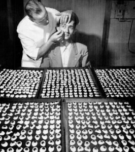 Fritz W. Jardon (standing) finds a match for a patient's good right eye. Today, each patient's ocular prothesis is customer made from start to finish.